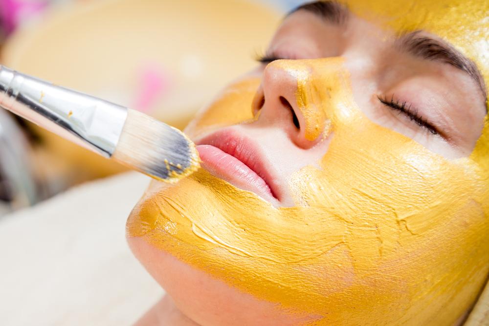 Mulher jovem tendo máscara de ouro aplicada em seu rosto para tratamento estético